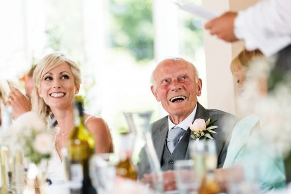 Grandfather laughing during wedding speeches