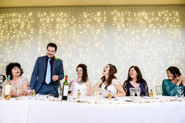 Two brides and family reacting to best man's wedding speech