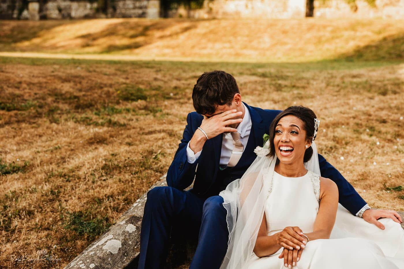 Bride and groom sitting on steps laughing and relaxed
