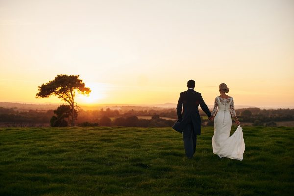 Bride and groom walking across field into sunset