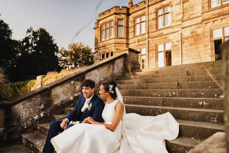 Bride and groom happy and laughing while sitting on steps of wedding venue