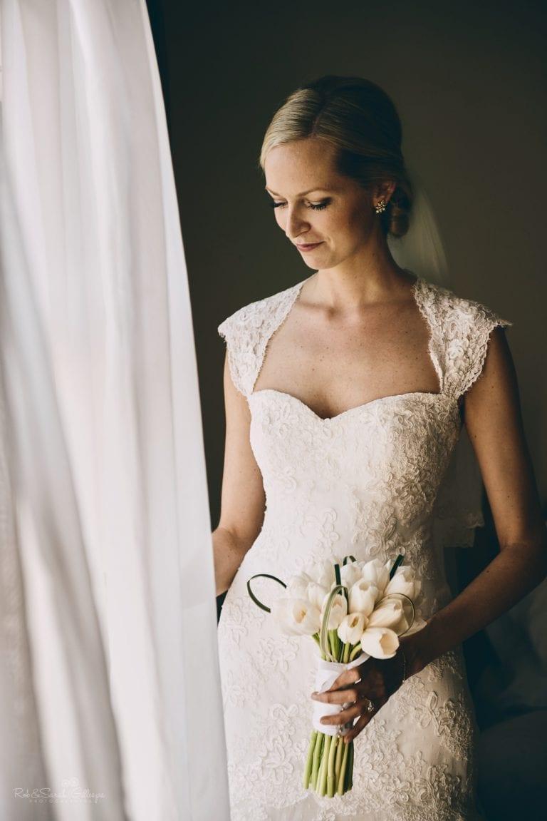 Beautiful bride portrait in window light as curtain billows