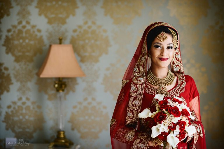 Bride in Bengali wedding dress poses for portrait