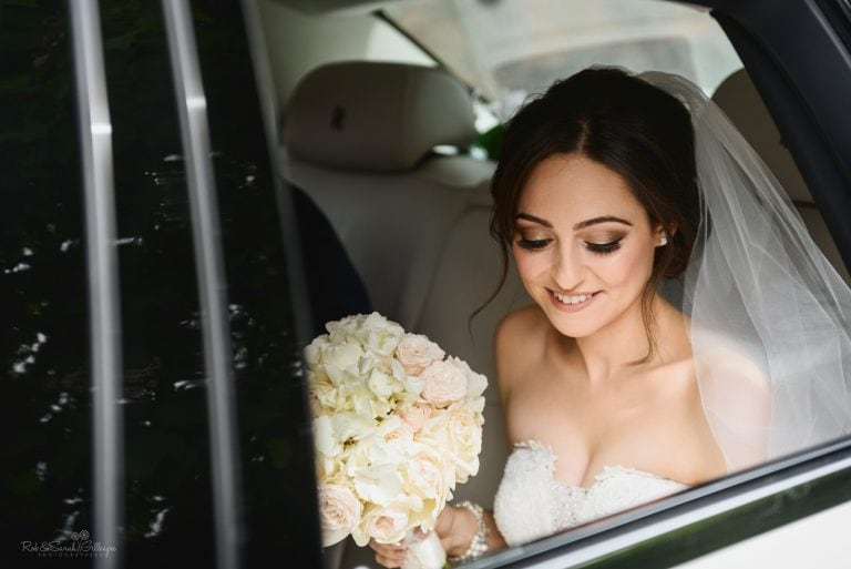 Bride smiling as she arrives at wedding in car