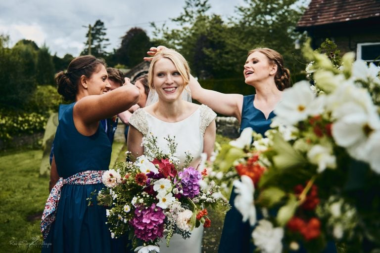 Bridesmaids pick confetti out of bride's hair as she laughs