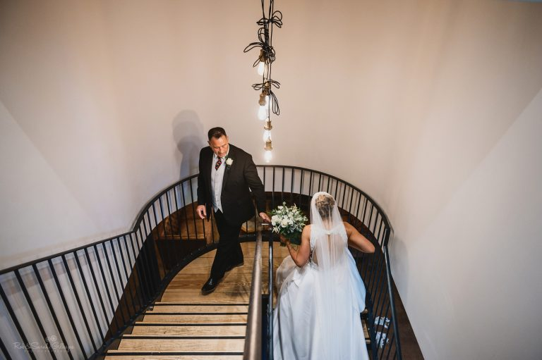 Bride and father walk up staircase to ceremony