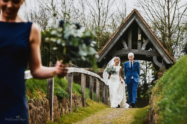 Bride and father walk along path to church wedding