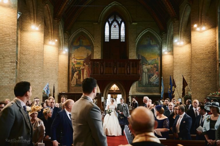 Bride and father enter beautiful church as groom watches