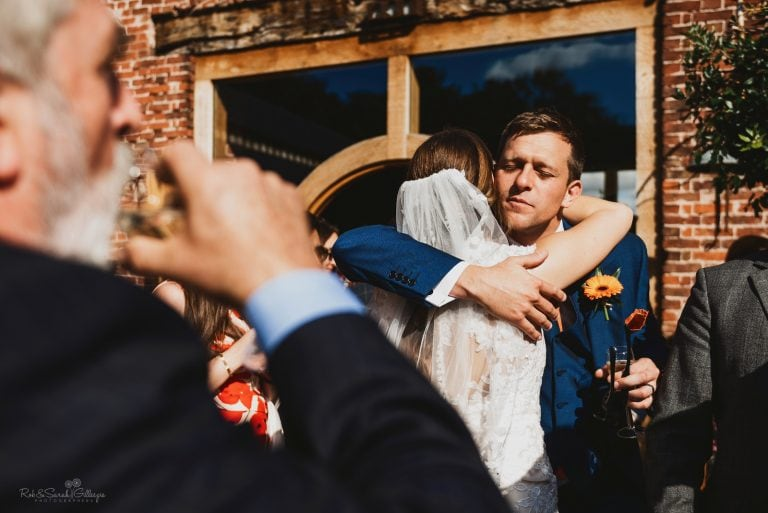 Guest hugs bride after wedding ceremony