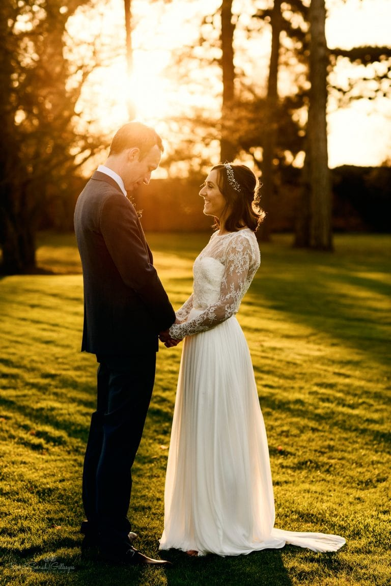 Bride and groom holding hands in beautiful evening sunlight