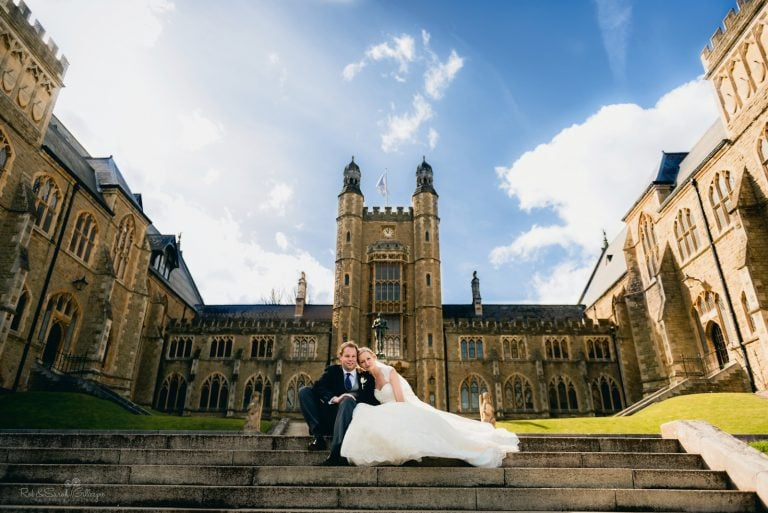 Bride and groom sitting on steps of wedding venue