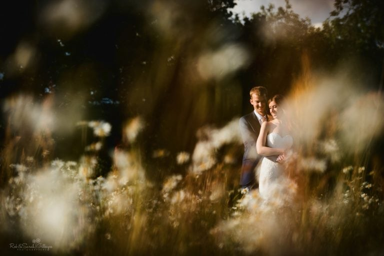 Bride and groom cuddle up in beautiful field