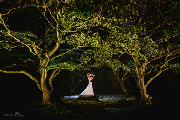 Bride and groom together under large trees at night