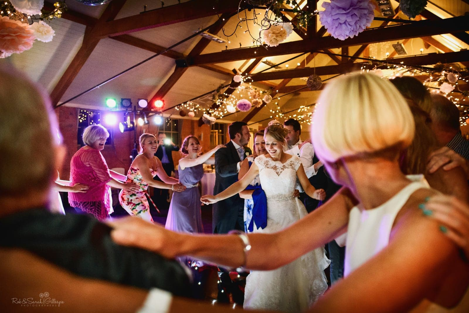 Bride and guests dancing the conga at wedding