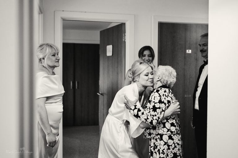 Bride kisses grandmother as they prepare for wedding