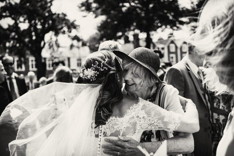 Grandmother hugs bride after wedding ceremony