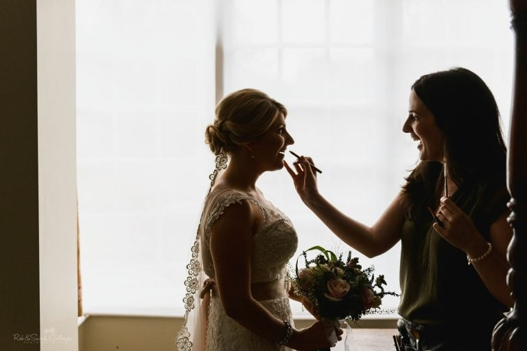 Bride silhouetted in window light as she has makeup applied