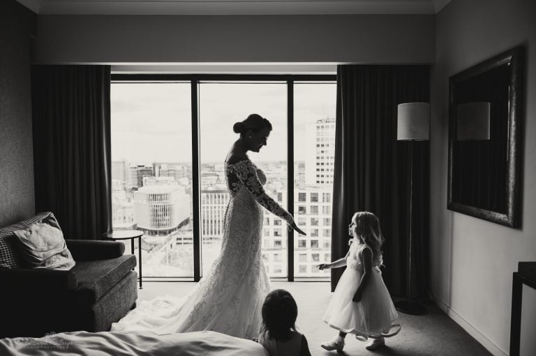 Bride holds out hand to flowergirl as they prepare for wedding