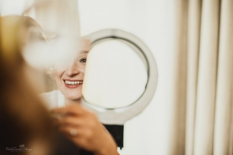 Bride smiling in small mirror as she has makeup applied before wedding