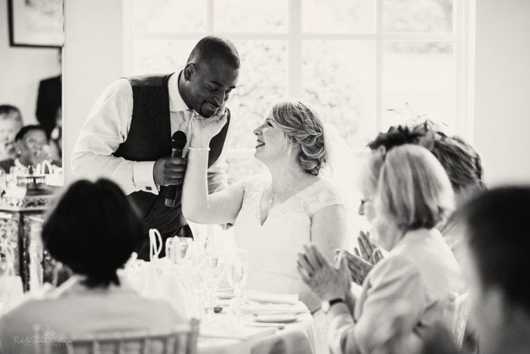 Bride smiling at groom as he gives wedding speech