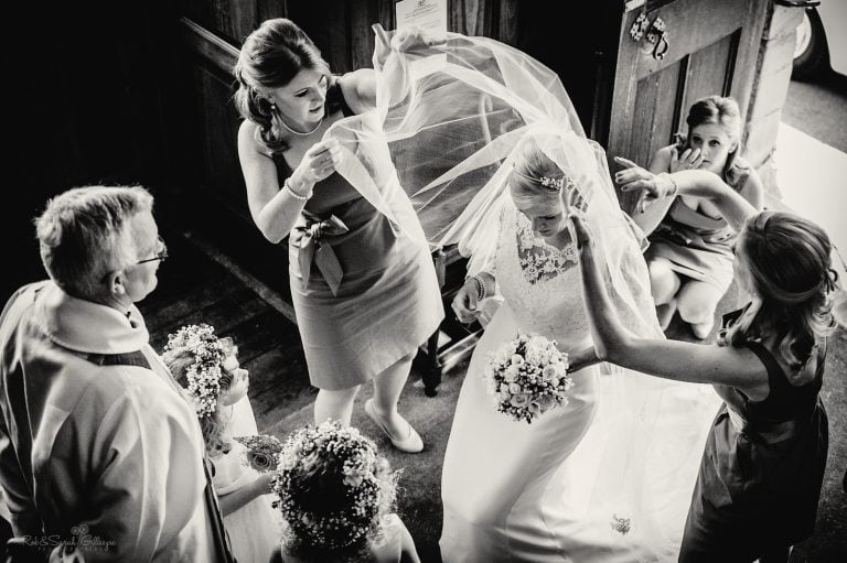 Bride has veil adjusted by bridesmaids as vicar talks to her before church wedding ceremony
