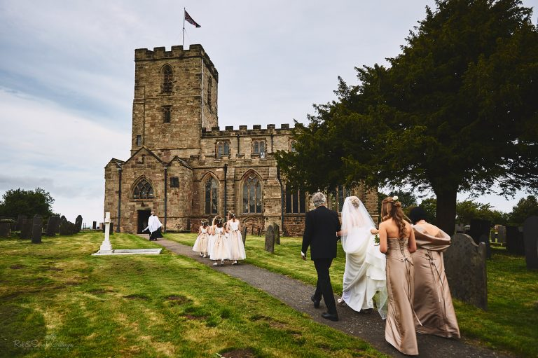 Bride and bridesmaids walk towards church for wedding ceremony