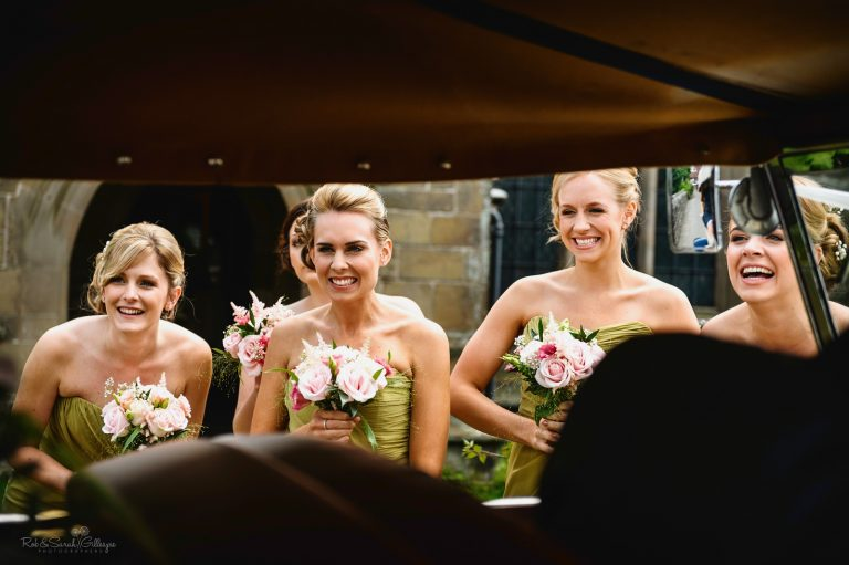 Bridesmaids react to seeing bride arrive at wedding in car