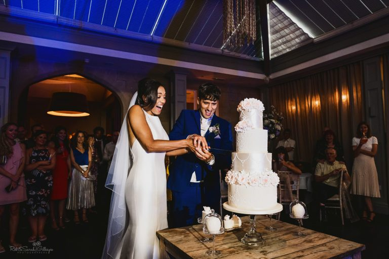 Bride and groom cut wedding cake as guests watch