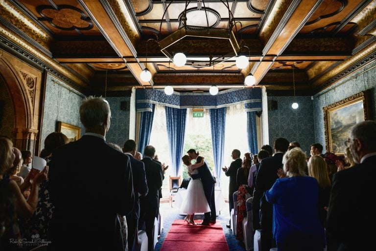 Couple kiss at end of wedding ceremony in beautiful hall