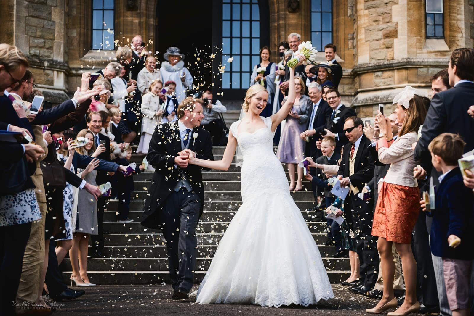 Bride and groom walk down steps as guests throw confetti