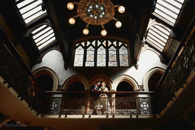Bride and groom on balcony inside beautiful wedding venue