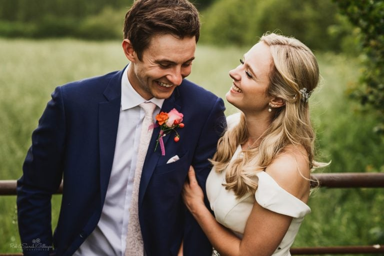 Bride and groom laughing together in beautiful fields