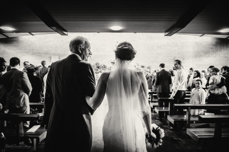 Dad glances at daughter as they walk up aisle for wedding ceremony