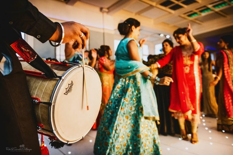Wedding guests dance as musicians play dhol drums