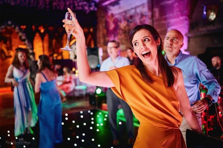 Wedding guest raises glass as she dances