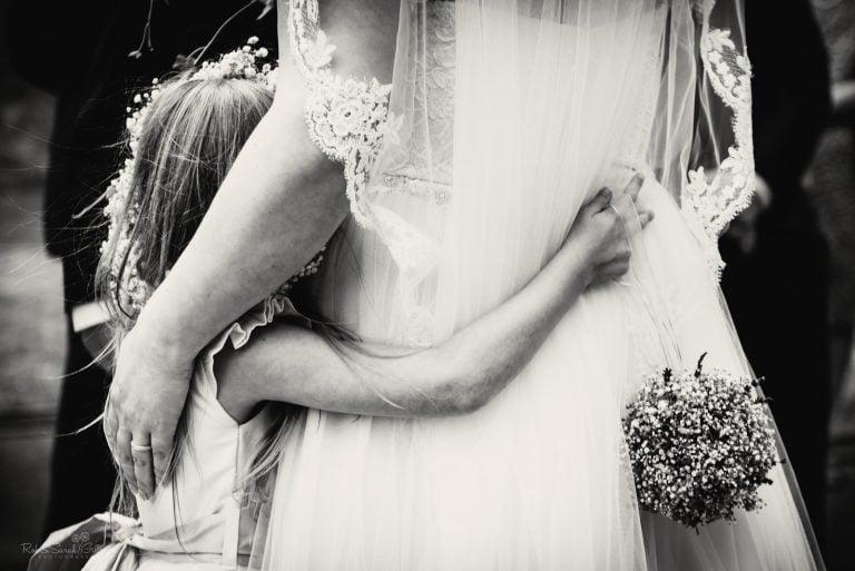 Flowergirl hugs bride