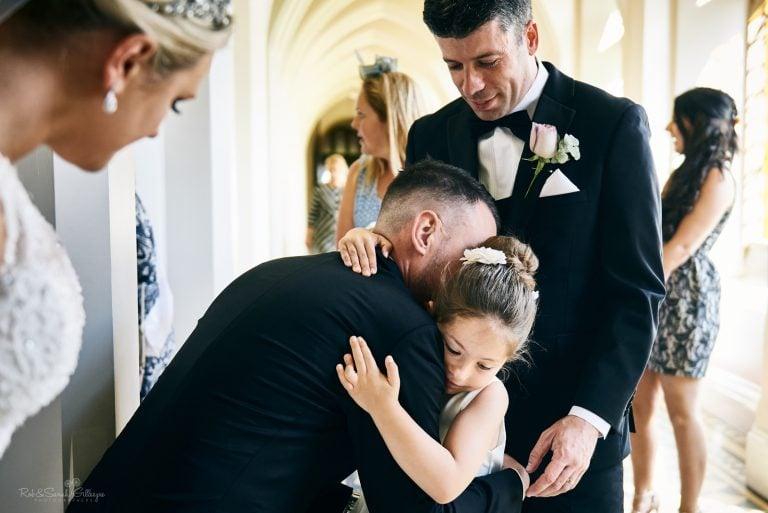 Young girl hugs groom during wedding reception