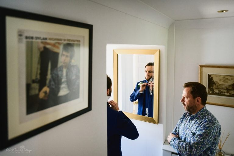 Groom adjusts tie in mirror as dad watches