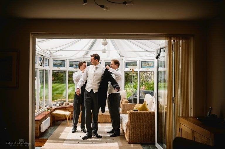 Groom helped by groomsmen as he prepares for wedding