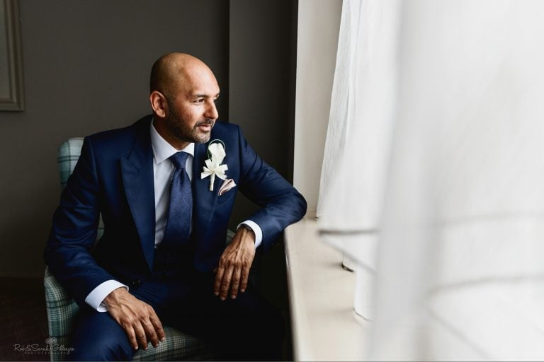 Groom seated in window light for portrait