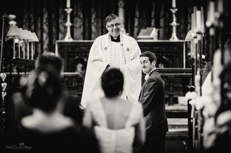 Groom turns to see bride walking up aisle as vicar looks on