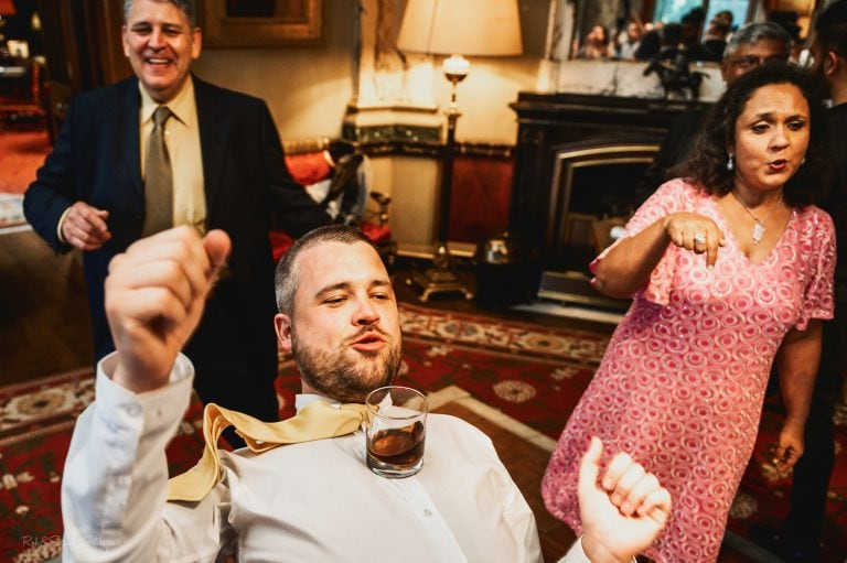 Wedding guest dances at wedding with drink balanced on his chest