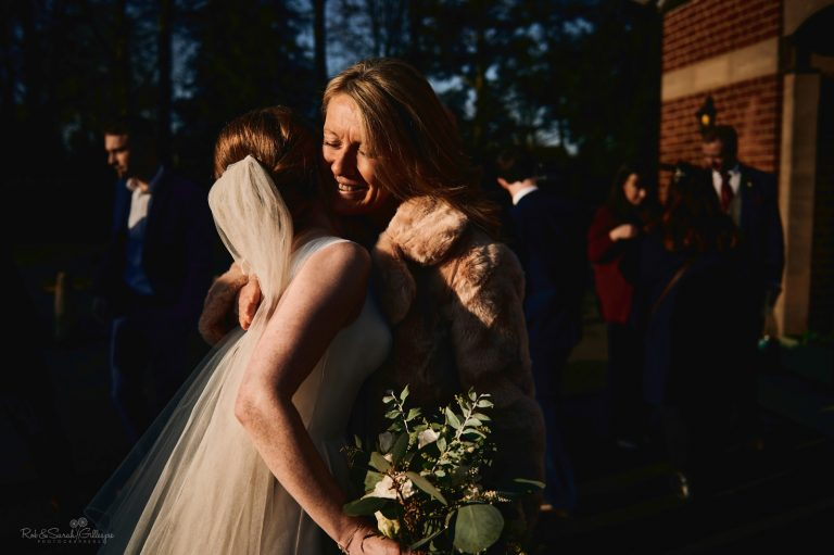 Bride hugged by wedding guest in beautiful winter light