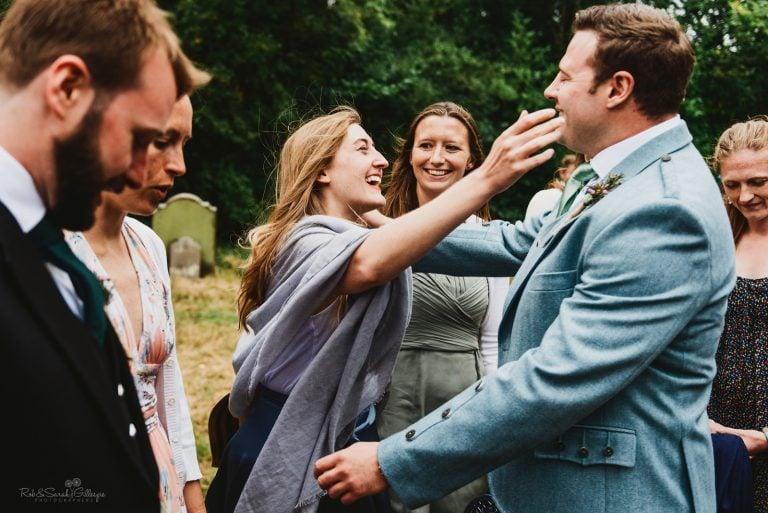Guest hugs groom before wedding ceremony