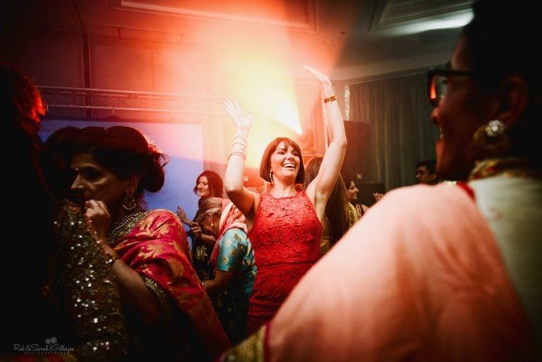 Wedding guest raises arms in air as she dances