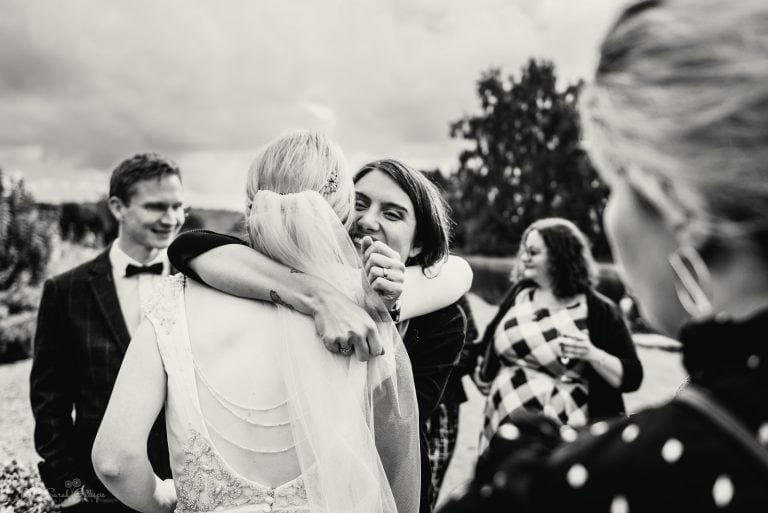 Bride hugged by smiling wedding guest