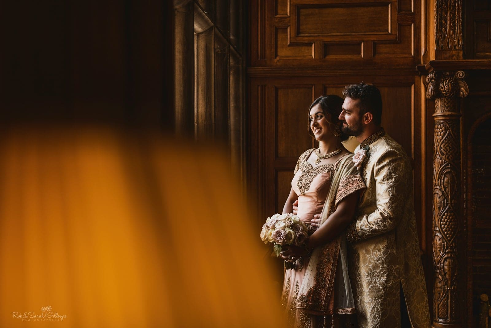 Bride and groom in Indian wedding outfits in beautiful window light