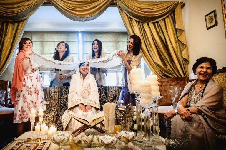 Bride and family laughing during Islamic wedding ceremony