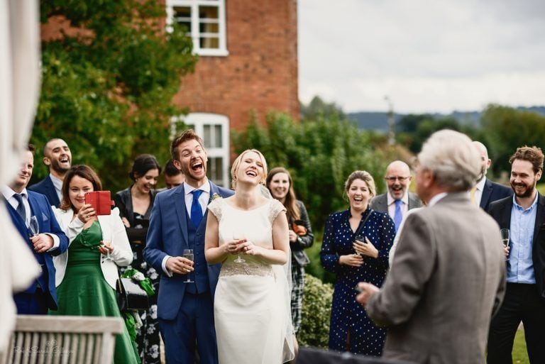 Bride and groom laughing during outdoor speech by grandfather