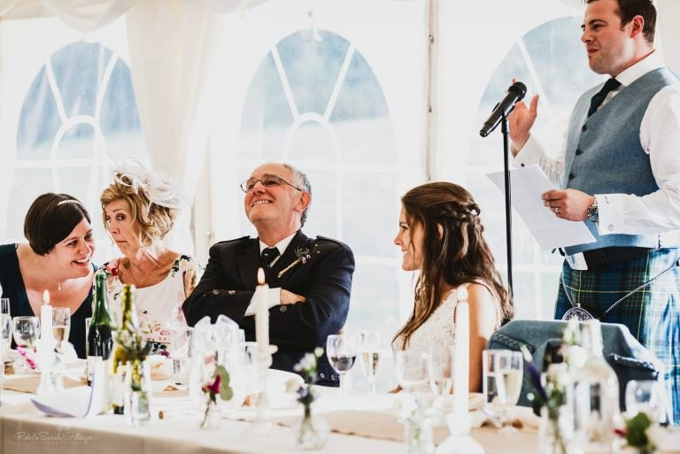 Guests pull funny faces as they laugh during wedding speeches